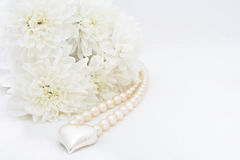 Chrysanteum, heart and pearl. Wedding background with chrysanteum, silver heart and pearl necklace Stock Photos