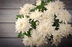 Chrysanthème blanc dans le pot de fleur avec le cadeau, carte de voeux, sur le backround en bois gris Image libre de droits