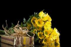 Chrysanthèmes et boîte-cadeau jaunes Image libre de droits