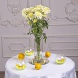 Chrysantheme auf dem Tisch mit Zitronen Lizenzfreie Stockbilder