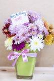 Chrysanthemen blüht im Vase des grünen Glases mit glücklicher Glückwunschkarte Lizenzfreies Stockbild