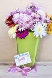 Chrysanthemen blüht im Vase des grünen Glases mit glücklicher Glückwunschkarte Lizenzfreie Stockfotografie