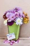 Chrysanthemen blüht im Vase des grünen Glases mit glücklicher Glückwunschkarte Stockfotos