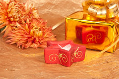Chrysanthemum, gift and red candle on gold Royalty Free Stock Image