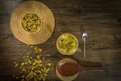 Chrysanthemum tea and honey bee on wood background Royalty Free Stock Photo