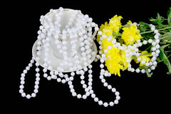 Chrysanthemums and beads are pearls on a black background. Yellow chrysanthemums and beads are pearls on a black background Stock Photo