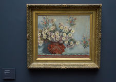 Chrysanthemums, by Claude Monet, 1878. Exhibited on a wall in the Musee d`Orsay is a framed painting by Claude Monet titled Chrysanthemums.  It was painted in Stock Photography
