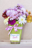 Chrysanthemums flowers in green  glass vase with thank you card Royalty Free Stock Images