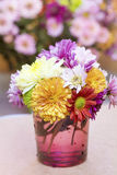 Chrysanthemums flowers in purple glass vase Stock Photography