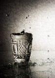 Chrystal杯与一个美好的结构的伏特加酒在玻璃桌上站立 免版税库存图片