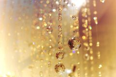 Chrystal chandelier with bokeh blurry background. Beautiful golden light Stock Images