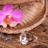 Chrystal pendulum. Pendulum with orchid on wooden table Stock Images