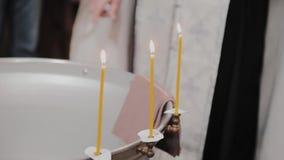 Chrzcielnicy dla ochrzczenia dzieci z płonącymi świeczkami w Ortodoksalnym kościół zdjęcie wideo