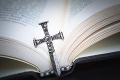 Chrześcijanin przecinająca kolia na Świętej biblii książce, Jezusowa religia conc obraz royalty free