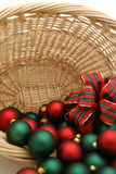 Chsrimas baubles. Red and green Christmas baubles spilling out of wicker basket stock photo
