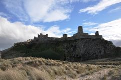 Château de Bamburgh dans le Northumberland à travers les dunes Photo stock