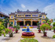 Chua Phap Bao Pagoda till och med en borggårdträdgård med blommor och bonsaiträd, Hoi An, Vietnam royaltyfri fotografi