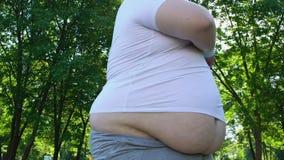 Chubby άτομο με τη μεγάλη κοιλιά που κάνει τις ασκήσεις πρωινού στο πάρκο πόλεων, workout καθημερινά φιλμ μικρού μήκους