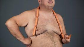 Chubby άτομο που τρώει τα λουκάνικα με την όρεξη, εθισμός τροφίμων, κίνδυνος διαβήτη Στοκ φωτογραφίες με δικαίωμα ελεύθερης χρήσης