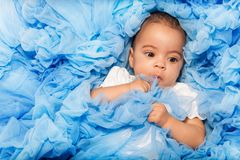Chubby African small baby laying on the blue cloth. Close-up view stock photo