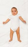 Chubby African small baby wearing white babygro Royalty Free Stock Photo