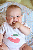 Chubby baby. With her hand in her mouth royalty free stock photos