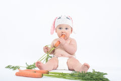 Chubby baby in rabbit hat with mouth and eyes wide open biting f Royalty Free Stock Photos