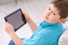 Chubby boy is busy with digital tablet Royalty Free Stock Photo
