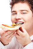 Chubby boy eating a slice of pizza Stock Photo