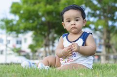 Chubby boy in grass. Chubby boy sitting in green grass of the parks Stock Images