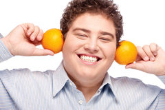 Chubby boy and orange. Happy chubby man with orange, isolated on white Stock Photo