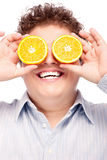 Chubby boy and orange. Happy man with slices of orange on his eyes, isolated on white background Stock Images