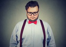 Upset young man looking down. Chubby eccentric man in bow time wearing glasses and holding head down in sorrow Stock Photography