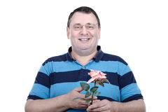 Chubby faced older man posing with rose in studio. Smiling chubby faced man holds a rose by hand and looking at the camera. Middle-aged guy wears glasses and Royalty Free Stock Photo