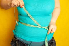 Chubby girl measures the circumference of her fat belly by centimeter tape stock photo