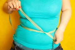 Chubby girl measures the circumference of her fat belly by centimeter tape. Colorful royalty free stock images