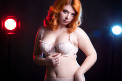 Chubby girl in underwear with two lights behind Royalty Free Stock Image