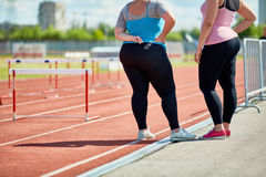 Chubby girls. Two plump friends in sportswear standing on racetrack of stadium stock photos