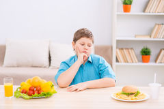 Chubby kid choosing food at the table Royalty Free Stock Photos