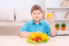 Chubby kid with juice and veggies Royalty Free Stock Image