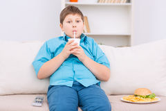 Chubby kid with junk food on the sofa. Unhealthy lunch. Chubby boy is sitting on the sofa and drinking from a papercup while plateful of junk food resting aside royalty free stock photography