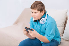 Chubby kid is playing video games Stock Images
