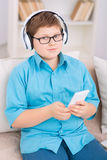 Chubby kid with the smartphone Stock Photos