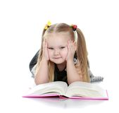 Chubby little blonde girl reading a book lying on Royalty Free Stock Photography
