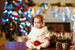 Chubby little cute baby girl in white dress sitting on the table Stock Photos