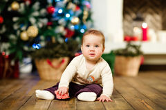 Chubby little cute baby girl 1 year old sitting on the floor in Stock Photos