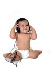 A chubby little girl listen to music. With headphones isolated on white background Royalty Free Stock Images