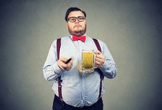 Chubby man with beer and TV remote stock images