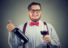Chubby man enjoying red wine. Funny man in bow tie holding bottle and wineglass looking content with taste Stock Photos