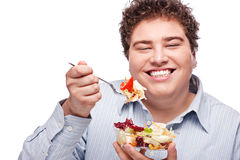 Chubby man with fresh salad. Happy young chubby man eating fresh salad with fork, isolate on white stock photo